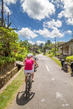 Young women is biking during rice fields cyclo tour in bali Royalty Free Stock Photos