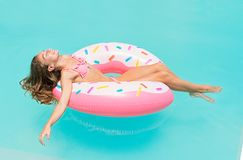 Young women in bikini lying down on an inflatable donut in swimming pool. Girl enjoys sunbathing on floating pool inflatable toy o. Young woman in bikini lying Royalty Free Stock Image