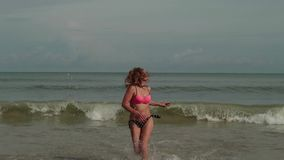 Young women in a bikini in a sea with waves enjoys sunbathing and beach vacation.  stock footage