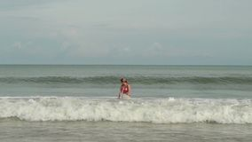 Young women in a bikini in a sea with waves enjoys sunbathing and beach vacation.  stock video footage
