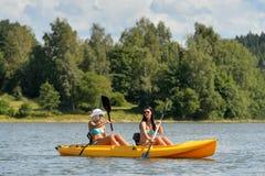 Happy girls kayaking on sunny day Stock Photos