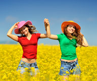 Young women on blooming rape field Stock Image