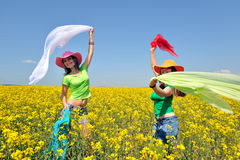 Young women on blooming rape field in summer Royalty Free Stock Photos