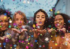 Young women blowing confetti from hands. Friends celebrating outdoors in evening at a terrace Royalty Free Stock Images
