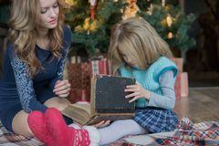 Mom and daughter spend leisure time reading a book at the Christmas tree royalty free stock photography