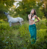 Young women in a blue long skirt and white bra at sunset in forest with a white horse  Stock Photo