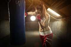 Young women boxing, hitting the boxing bag - on the attic