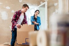 Young woman bringing open box moving in with her boyfriend. Young women bringing an open heavy cardboard box while moving in with her boyfriend into their new Royalty Free Stock Images