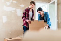 Young woman bringing open box moving in with her boyfriend into Stock Photography