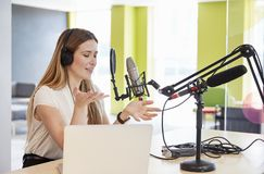 Young woman broadcasting in a studio gesturing, close up stock photo