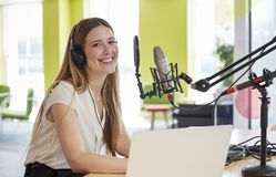 Young woman broadcasting in a studio smiling to camera royalty free stock images