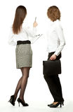 Young women at a business meeting. Young businesswomen at a business meeting/negotiations/conference/presentation; rear view of two businesswomen holding royalty free stock image