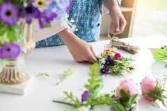 Young women business owner florist making or Arranging Artificial flowers vest in her shop, craft and hand made concept.  royalty free stock image