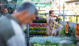 Young woman buying flowers at a garden center Stock Photos