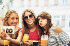 Young women in a cafe after a shopping make selfie photo. Three young women in a cafe after a shopping make selfie photo royalty free stock photography