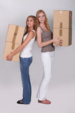 Young women carrying boxes Stock Photos