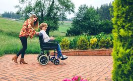 Woman carrying her mother in a wheelchair stock images