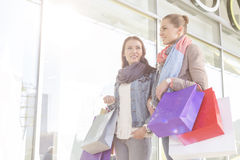 Young women carrying shopping bags by store Royalty Free Stock Photo
