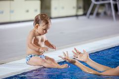 Young woman catching little son sitting poolside Stock Photos
