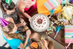 Young women celebrating with cake and champagne a birthday. High-angle view of cheerful young women celebrating with cake and champagne the birthday anniversary royalty free stock images