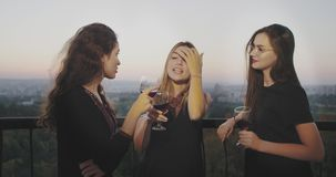 Young women chatting and drinking wine on the top of building with amazing sunset view. Young women chatting and drinking wine on the top of building with stock video