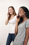 Young women chatting on phone. Two young woman chatting on phone, selective focus Royalty Free Stock Photo