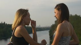 Young women chatting standing on a bridge across the river stock video