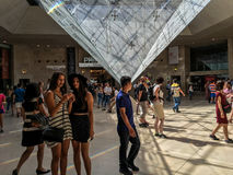 Young women check selfie shots in front of upside down pyramid in Louvre Carrousel Royalty Free Stock Photography