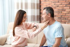 Young woman checking mature man`s pulse with fingers. Young women checking mature man`s pulse with fingers at home stock photography