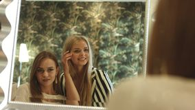 Young women checking their appearance and smiles in front of the mirror