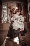 Woman with a child in her arms, dressed in clothes in the style of steampunk. Young women with a child in her arms, dressed in clothes in the style of steampunk stock image