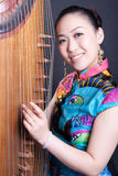 Young women and Chinese zither. Young women petting Chinese zither Stock Image