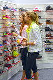 Young women in the department of sports shoes Royalty Free Stock Photography