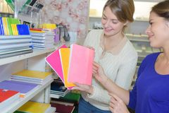 Young women choosing copy-books for writing in stationary shop. Female Stock Images
