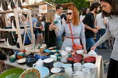 Young women choosing pottery on the stand of crowded weekend street Stock Photo