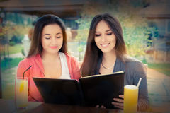 Young Women Choosing from a Restaurant Menu Royalty Free Stock Image