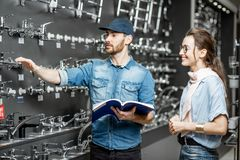 Woman with salesman in the plumbing shop. Young women choosing sanitary taps standing with salesman near the showcase of plumbing shop royalty free stock image