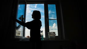Young Women cleaning a window. Silhouette of a woman working with a rag stock video