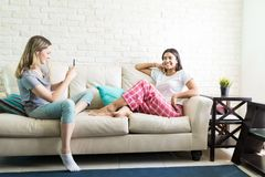 Woman Clicking Picture Of Friend Hanging Out At Home. Young women clicking picture of happy friend hanging out at home royalty free stock photography