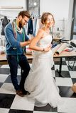 Woman fitting wedding dress at the tailor studio. Young women client fitting wedding dress with men tailor standing at the sewing studio Stock Image