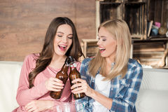Young women clinking beer bottles while sitting on couch. Happy young women clinking beer bottles while sitting on couch Stock Image