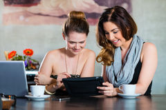 Young women or colleagues sitting in a cafe or restaurant Royalty Free Stock Photos