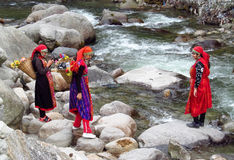 Young women in colorful clothes on a river bank with flowers Stock Images