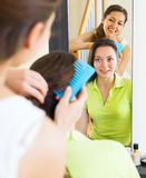 Young women combing the hair Stock Images