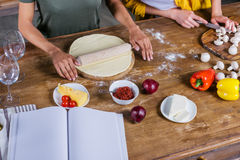 Young women cooking pizza while standing together at kitchen table with blank cookbook Royalty Free Stock Photo