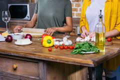Young women cooking pizza together in kitchen Stock Images