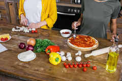 Young women cooking pizza together in kitchen Royalty Free Stock Images