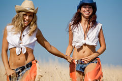 Young women in costumes of cowboys outdoors Stock Photos