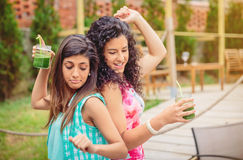 Young women couple with healthy drinks dancing Royalty Free Stock Photos