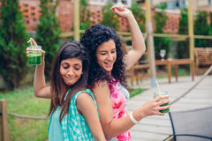 Young women couple with healthy drinks dancing outdoors Stock Photos